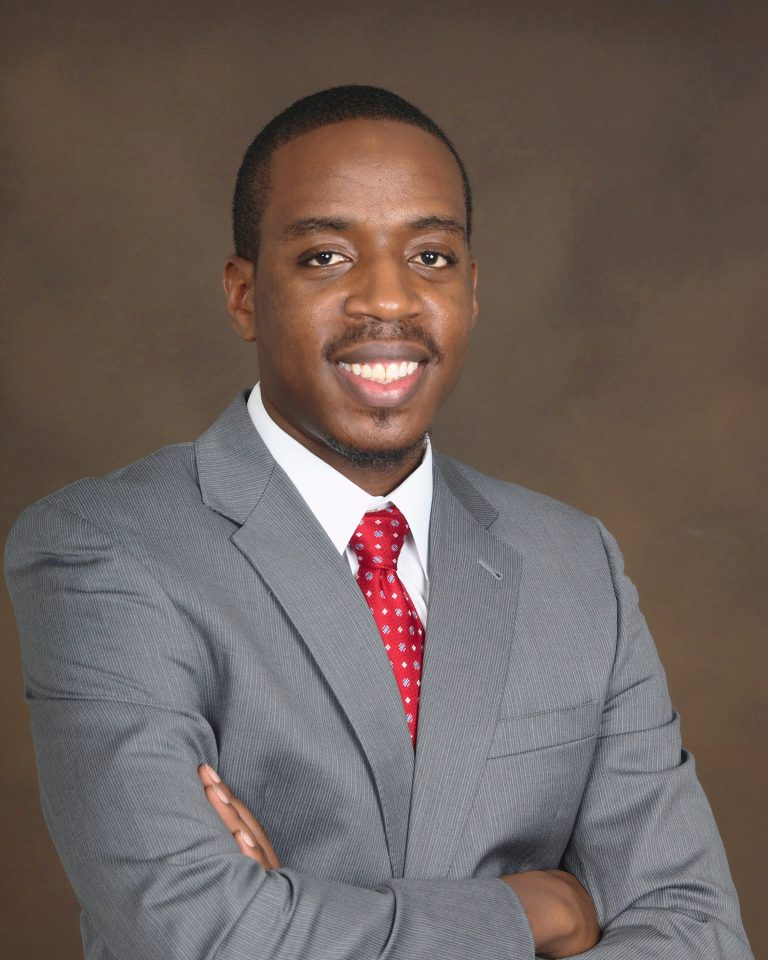 Attorney, Paul Agbeyegbe standing against a brown background with a gray suit, wearing a red tie and smiling with his arms folded.